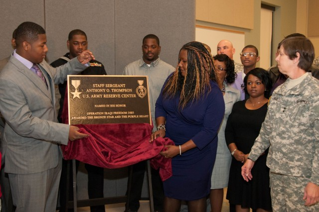 "Valerie and Jaykwon Thompson, wife and son of fallen Soldier Staff Sgt. Anthony Thompson, reveal the plaque for the Orangeburg Army Reserve Center named after Anthony Feb. 21. Anthony, a native of Orangeburg, died in combat while supporting Operation Iraqi Freedom in 2003. ""Naming the center in a public event, like the one we are hosting, is to honor both the service of Staff Sgt. Thompson and the support from this community and Army families,"" said Maj. Gen. Janet Cobb, commander, 81st Regional Support Command"
