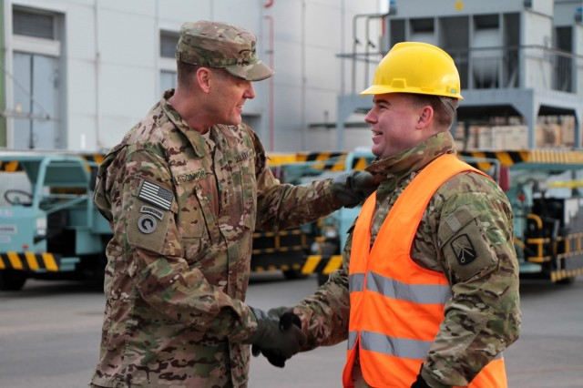 """RIGA, Latvia -- Maj. Gen. John R. O'Connor, commanding general of the 21st Theater Sustainment Command, U.S. Army Europe, meets with Capt. Robert Yauger, commander of the 624th Movement Control Team, 16th Sustainment Brigade, 21st TSC, as port officials, stevedores, leaders and Soldiers download cargo from the transportation vessel """"Liberty Promise"""" March 9 at the Riga Universal Terminal docks in support of Operation Atlantic Resolve. The ongoing mission exemplifies U.S. and NATO commitment to the region, builds allied capability and interoperability, and bolsters regional security and stability. Soldiers of the 1st Armor Brigade Combat Team, 3rd Infantry Division, will employ the tanks and M2A3 Bradley Fighting Vehicles unloaded the same day during a training rotation in eastern and central Europe. The delivery marks the first time American forces have shipped main battle tanks directly from the U.S. to the Riga terminal."""