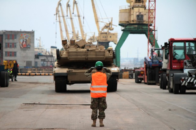 """RIGA, Latvia -- A Soldier with the 386th Movement Control Team, 39th Transportation Battalion, 16th Sustainment Brigade, 21st Theater Sustainment Command, guides an M1A2 Abrams Main Battle Tank from the transportation vessel """"Liberty Promise"""" March 9 at the Riga Universal Terminal docks. Port officials, stevedores, and allied leaders and Soldiers downloaded a variety of weapons systems, including the tanks, M2A3 Bradley Fighting Vehicles, unit gear and other cargo in support of Operation Atlantic Resolve. The ongoing mission exemplifies U.S. and NATO commitment to the region, builds allied capability and interoperability, and bolsters regional security and stability. Soldiers of the 1st Armor Brigade Combat Team, 3rd Infantry Division, will employ the vehicles during a training rotation in eastern and central Europe."""