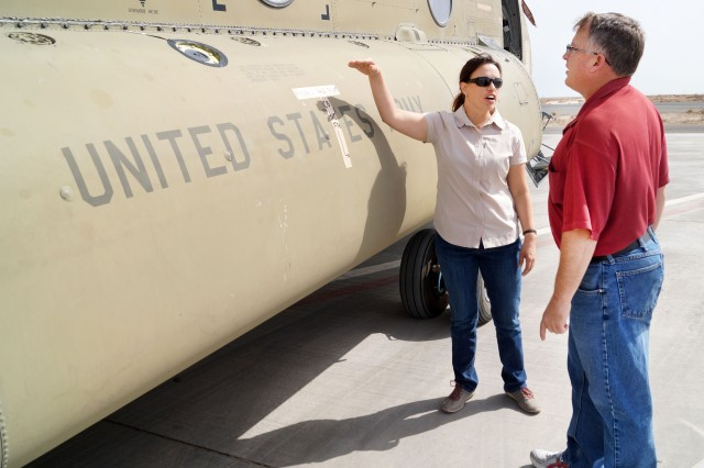Carrie Guilliams, a Communications and Electronics Command avionics logistics assistance representative, and David S. Resch, operations officer, Aviation and Missile Command, discuss components of a Ch-47 Chinook helicopter at the Aerial Port of Debarkation, Kuwait, Feb. 19. (Photo by Sgt. William Taylor, 402nd AFSB Public Affairs)