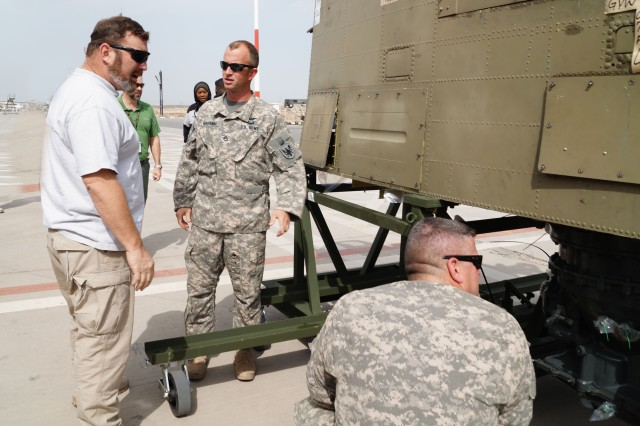 Curtis Latta, an Aviation and Missile Command logistics assistance representative, and Soldiers from the 90th Aviation Support Battalion and 603rd ASB, 11th Aviation Command, discuss components of a CH-47 Chinook helicopter at the Aerial Port of Debarkation, Kuwait, Feb. 19. (Photo by Sgt. William Taylor, 402nd AFSB Public Affairs)