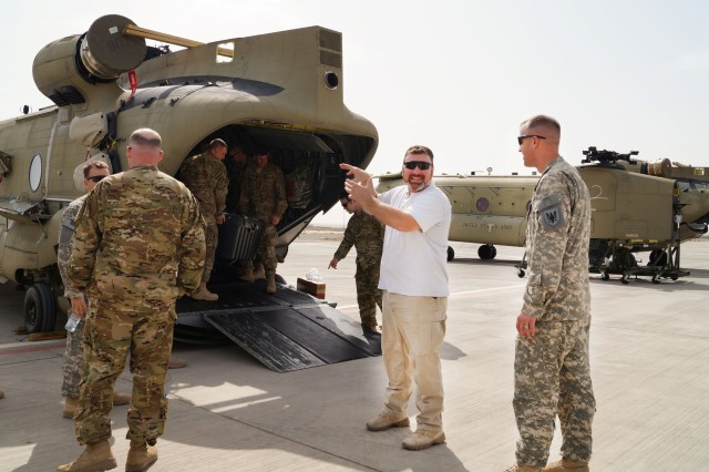 Curtis Latta, an Aviation and Missile Command logistics assistance representative, and a Soldier from the 11th Aviation Command, discuss components of a Ch-47 Chinook helicopter at the Aerial Port of Debarkation, Kuwait, Feb. 19. (Photo by Sgt. William Taylor, 402nd AFSB Public Affairs)