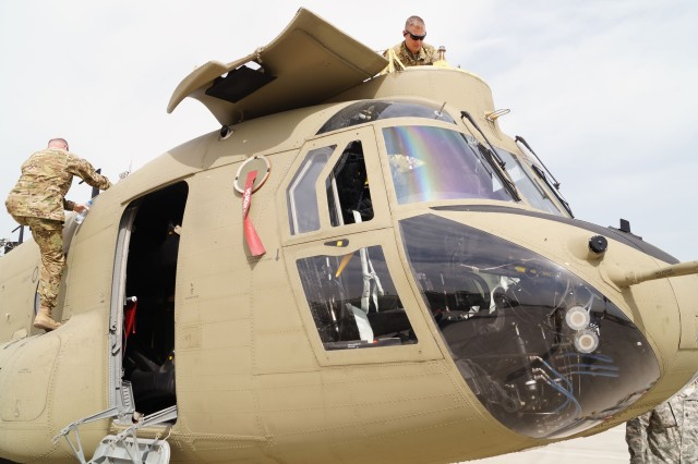 Soldiers from the 2nd Battalion, 3rd General Support Aviation Regiment, inspect a Ch-47 Chinook helicopter at the Aerial Port of Debarkation, Kuwait, Feb. 19. (Photo by Sgt. William Taylor, 402nd AFSB Public Affairs)
