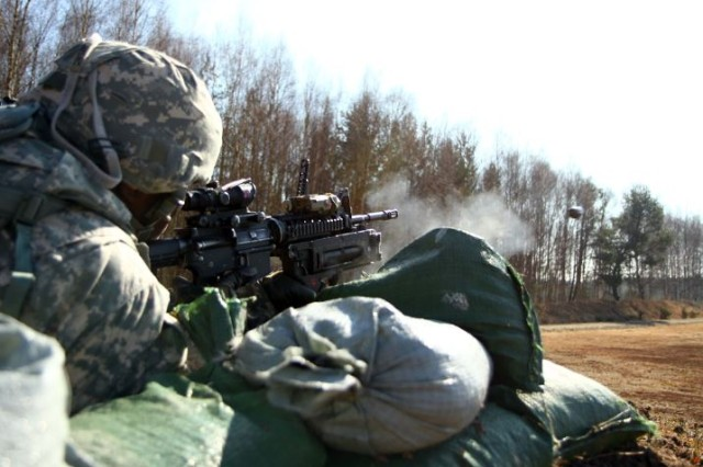 Spc. Blair Flowers, an information technology specialist with the 361st Civil Affairs Brigade, 7th Civil Support Command, fires a M320 Grenade launcher at a combined training activity with the 173rd Airborne Brigade at Grafenwoehr, Germany, March 10, 2015.