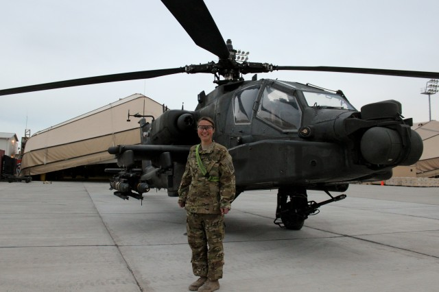 Spc. Edie Belk of the 82nd Airborne Division with a AH-64D Apache Longbow attack helicopter at Bagram Airfield, Afghanistan. Belk is the only female Apache crew chief in the unit.