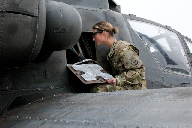 Spc. Edie Belk of the 82nd Airborne Division performs checks on a AH-64D Apache Longbow attack helicopter at Bagram Airfield, Afghanistan. Belk is the only female Apache crew chief in the unit.