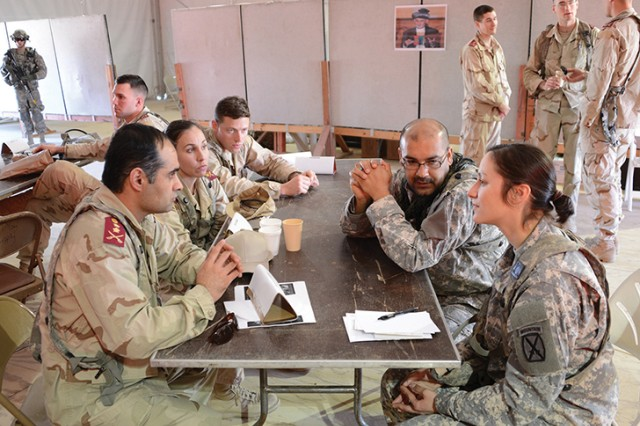 Capt. Jennifer Menard, public affairs officer of 2nd Brigade Combat Team, 10th Mountain Division (LI), uses an interpreter to conduct a meeting with a role player acting as an Afghan military official during a mission readiness exercise Feb. 13.