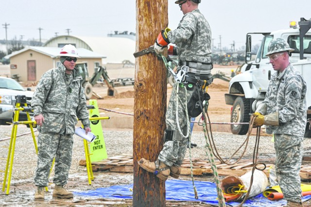 "Sgt. 1st Class Rustin ""Nemo"" Owen, Prime Power School instructor, evaluates Sgt. Travis Polak, 249th Engineer Battalion, during the Lineman's Rodeo. Sgt. John Neary, 249th Engr. Bn., is serving as Polak's ground man."