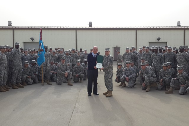 Pom-Chae Yi (left) accepts a 50-year certificate from Col. Kris Arnold the 501st Military Intelligence Brigade commander, at Camp Humphreys, South Korea, Feb. 22. (Photo by Capt. Danny Z. Zhu)