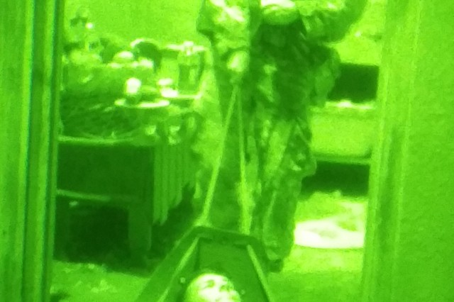 A Soldier assigned to 2nd Battalion, 35th Infantry Regiment, 3rd Brigade Combat Team, 25th Infantry Division, pulls a simulated casualty into a safe building during a night operation of Exercise Lightning Forge at Marine Corp Training Area-Bellows on Feb. 27, 2015. (U.S. Army photo by Sgt. Brian C. Erickson, 3rd Brigade Combat Team Public Affairs Office)