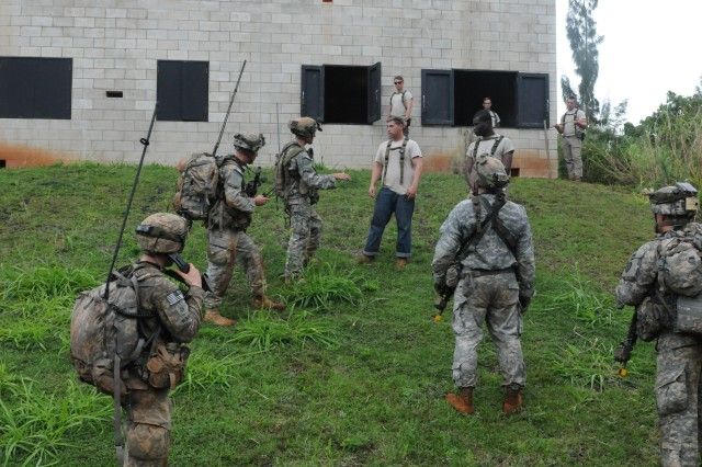Soldiers assigned to 2nd Battalion, 35th Infantry Regiment, 3rd Brigade Combat Team, 25th Infantry Division, talk to an Ari National (role player) during a Non Combatant Evacuation Operation of Exercise Lightning Forge at Kahuku Training Area on Feb. 28, 2015. (U.S. Army photo by Sgt. Brian C. Erickson, 3rd Brigade Combat Team Public Affairs Office)