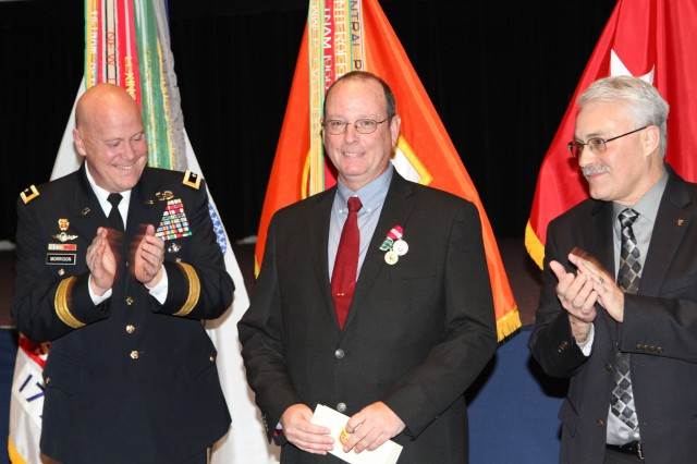 John Dolak, NETCOM G-3/5/7 (center), earned the title of NETCOM 2014 Civilian of the Year, during a ceremony in the Greely Hall Auditorium March 12. Celebrating Dolak's selection are NETCOM Commanding General, Maj. Gen. John Morrison Jr., and Daniel Bradford, NETCOM Deputy to the Commander/Senior Technical Director/Chief Engineer. Dolak was selected in part for his outstanding support as Team Lead for the Find & Fix/Pro-active Analysis & Quick Reaction mission and the Fort Hood network performance enhancements.