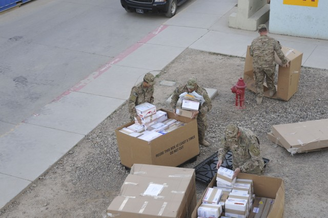 Soldiers, with 1st Infantry Division Headquarters and Headquarters Battalion, collect mail outside the Combined Joint Forces Land Component Command-Iraq mail room March 4, 2015. Soldiers of the 1st Inf. Div. re-established a military mail system that was dormant in the country since 2011.