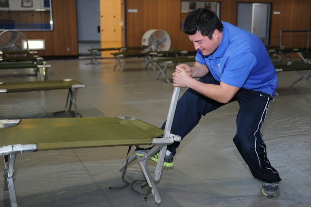 Gregory Zaboski, a sports specialist for the Camp Zama Moral Welfare and Recreations, sets up sleeping cots at Yano Fitness Center, as a part of the Mass Care Facility during the 4th annual earthquake functional exercise conducted March 12 on the Camp Zama installation. (U.S. Army photos by Noriko Kudo)