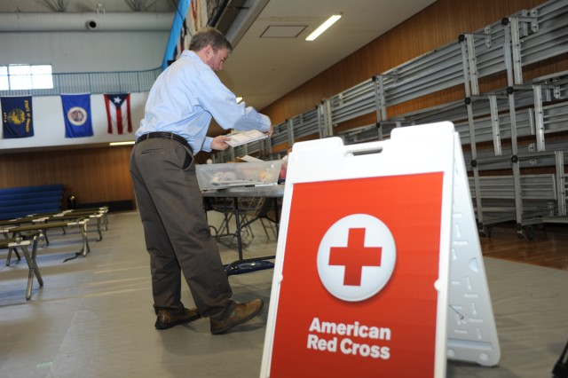 Paul Butler, station manager for the Camp Zama American Red Cross, prepares an information booth at the Mass Care Facility set up at Yano Fitness Center during the 4th annual earthquake functional exercise conducted March 12 on the Camp Zama installation. (U.S. Army photos by Noriko Kudo)