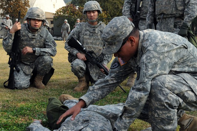 Sgt. Johnston Albert Jr. (right) and Cpl. Il Shin Kim, both from the 501st Special Troops Battalion, 501st  Sustainment Brigade, demonstrate basic lifesaving skills to U.S. and KATUSA Soldiers during Sergeant's Time Training in October 2014 on Yongsan Garrison, Republic of Korea.