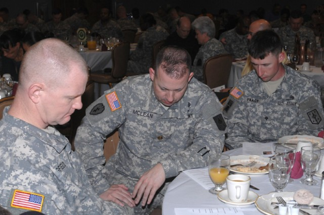 Soldiers spend time praying for the military during the National Prayer Breakfast Tuesday at Pershing Community Center.