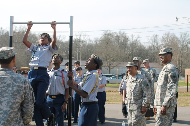 Buckhorn cadet Chanel Shelton gives it her all during the pullup contest, while Army Materiel Command commander Gen. Dennis L. Via and Command Sgt. Maj. James Sims observe. Shelton won the contest for females with 12 pullups.