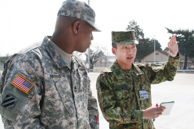 1st Lt. Matsuaki Saruya, 1st Logistics Support Regiment, Japanese Ground Self Defense Force, and Sgt. 1st Class Luis Rivera, noncommissioned officer in charge, Army Field Support Battalion-Northeast Asia, discuss the Inland Petroleum Distribution System during a logistics terrain walk at Sagami General Depot, Japan. (Photo by Arika Morita, AFSBn-NEA)