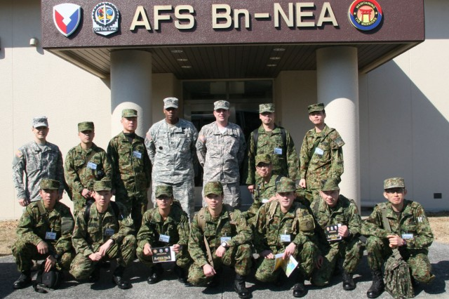 Members of U.S. Army Japan's Cooperative Exchange Program Class #75 and Army Field Support Battalion-Northeast Asia, pose outside the battalion's headquarters at Sagami General Depot following a tour of Army Prepositioned Stock-4 facilities. (Photo by Arika Morita, AFSBn-NEA)