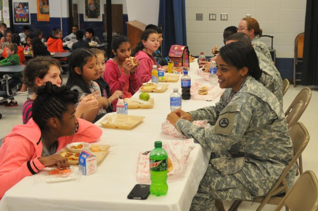 Third Sustainment Command (Expeditionary) Human Resources Officer, Capt. Victoria Parrish, eats lunch with students in Karen Gonterman's class at Jeffersontown Elementary School, March 20. The students wrote letters to 3rd ESC Soldiers for more than six months during the unit's recent deployment to Afghanistan. (U.S. Army photo by Staff Sgt. Justin Silvers)