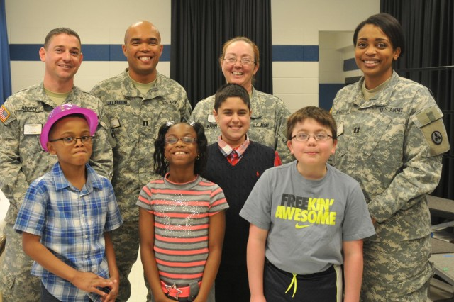 (From left) Third ESC Public Affairs Officer, Maj. Jared Auchey, 3d ESC Operational Law Attorney, Capt. Matthew Jalandoni, 3rd ESC Sexual Assault Response coordinator, Sgt. 1st Class Tonya Karm, and 3rd ESC Human Resources Officer, Capt. Victoria Parrish, pose with students from Jeffersontown Elementary School. The students wrote letters to 3rd ESC Soldiers during the unit's recent nine-month deployment to Afghanistan. (U.S. Army photo by Staff Sgt. Justin Silvers)