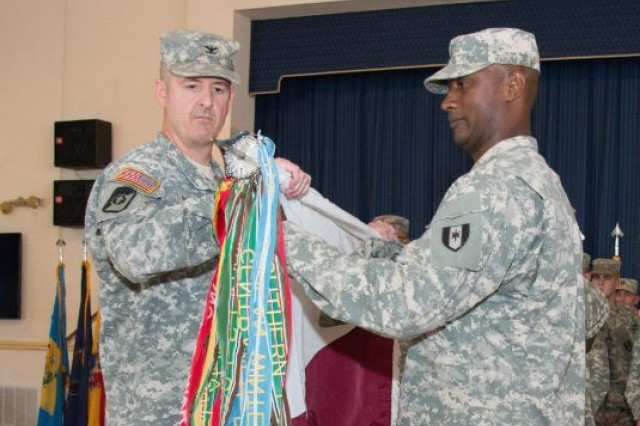 Col. Patrick Garman, left, commander of the 1st Area Medical Laboratory, uncases the unit colors with Sgt. Maj. Kenneth Petty, senior enlisted leader, on Aberdeen Proving Ground, Md., March 23, 2015.