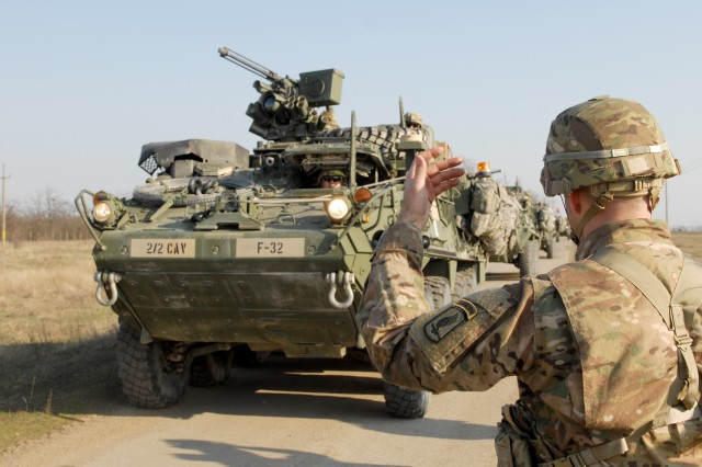 U.S. Army Maj. Scotty Autin, operations officer for the 173rd Airborne Brigade Special Troops Battalion, ushers in a Stryker-armored vehicle convoy, from 2nd Squadron, 2nd Cavalry Regiment, as part of a forward passage of line movement at Smardan Training Area, Romania, March 24, 2015. Saber Junction 15 includes 5,000 troops from 17 NATO allied and partner nations.