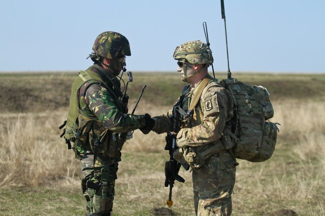 A U.S. Army paratrooper, assigned to the 173rd Airborne Brigade, greets a Romanian soldier, from the 280th Brigade, at Smardan Training Area, Romania, March 24, 2015. The 173rd Airborne Brigade conducted an airborne operation as part of the combined early-entry Exercise Saber Junction 15.