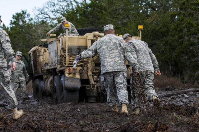 Soldiers, from the 277th Engineer Company (Horizontal), located in Camp Bullis, Texas, help recover an M984 Wrecker truck stuck in the mud, belonging to the 31st Trailer Transfer Point, a detachment from Houston, Texas, during a recovery operation at Camp Bullis, March 22, 2015.