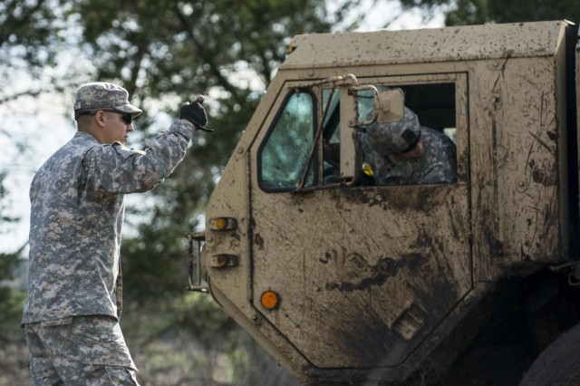 Sgt. Robert Gonzales, maintenance squad leader for the 277th Engineer Company (Horizontal), helps guide a recovery vehicle to free up an M984 Wrecker truck stuck in the mud, at Camp Bullis, March 22, 2015.