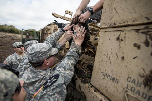 Soldiers, from the 277th Engineer Company (Horizontal) and 31st Trailer Transfer Point, lift a winch block onto an M984 recovery vehicle during a muddy recovery operation at Camp Bullis, Texas, March 22, 2015.