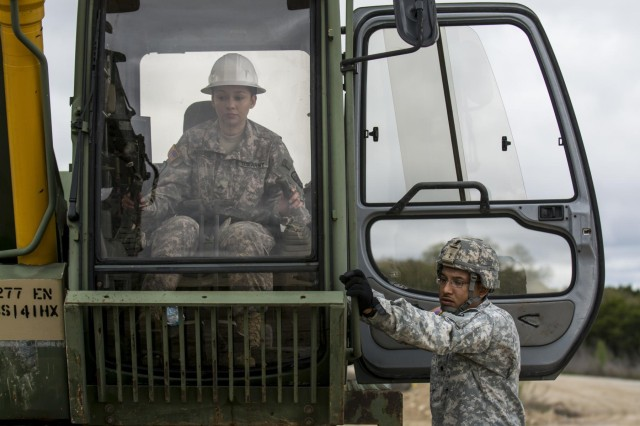 Cpl. Christelle Arriaga operates a hydraulic excavator, at the guidance of a fellow Soldier, during a battle assembly at Camp Bullis, Texas, March 22, 2015. The Soldiers are assigned to 277th Engineer Company (Horizontal).