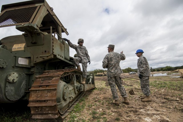 Sgt. Aaron Lawson, center, squad leader for the 277th Engineer Company (Horizontal), talks with two of his Soldiers during a battle assembly weekend at Camp Bullis, Texas, March 22, 2015.