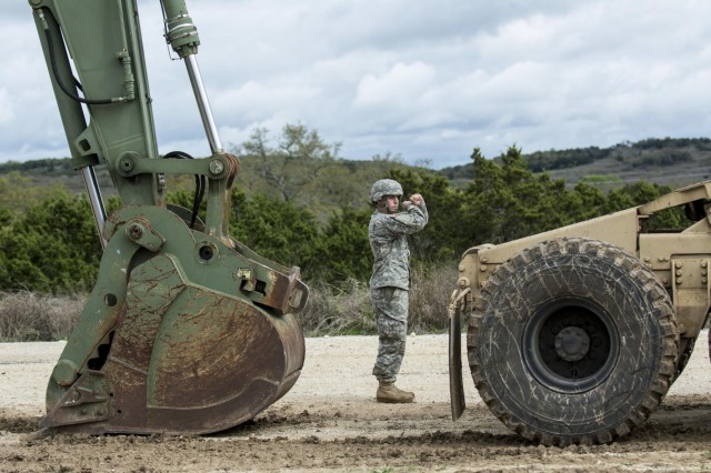 A Soldier, from the 277th Engineer Company (Horizontal), gives ground-guiding directions to a driver while staging vehicles during a battle assembly weekend at Camp Bullis, Texas, March 22, 2015.
