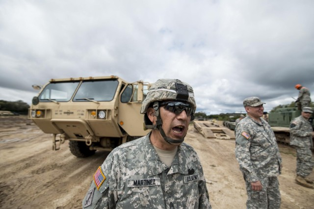 Staff Sgt. Raul Martinez, a squad leader with the 277th Engineer Company (Horizontal), calls out to fellow Soldiers while staging vehicles at Camp Bullis, Texas, March 22, 2015.