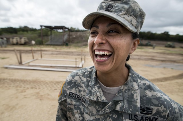 Sgt. 1st Class Lucia Estrada, platoon sergeant for the 277th Engineer Company (Horizontal), laughs among her Soldiers during vehicle staging at Camp Bullis, Texas, March 22, 2015.