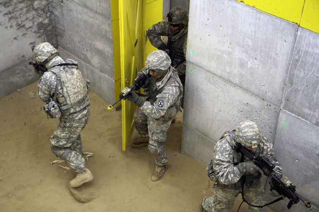 A four-man team of B Company Soldiers tactically enters a room at the Military Operations in Urban Terrain site March 19 during a 2nd Battalion, 87th Infantry Regiment, 2nd Brigade Combat Team field training exercise at Fort Drum. Before entering, each team member knows which way to turn and where to point their weapon muzzle to maximize control of the room and minimize casualties.