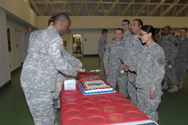 Soldiers observe the ceremonial cake cutting following the Maneuver Support Center of Excellence and Fort Leonard Wood Women's History Month Observance March 19 at Nutter Field House.