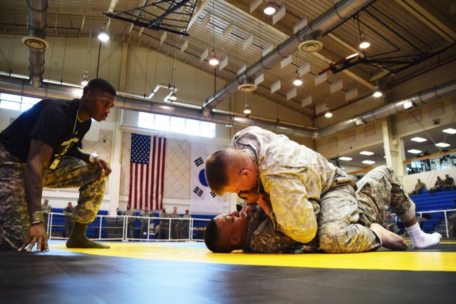 Sgt. Devon McMullen evaluates two 35th Air Defense Artillery Brigade Soldiers during the brigade Modern Army Combatives tournament at Camp Carroll fitness center March 25, 2015. McMullen was one of seven referees for the event and is Tactical Combatives certified. (Photo by: Staff Sgt. Heather A. Denby, 35th ADA Public Affairs)