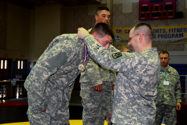Lt. Col. Jeffrey Adams, commander of 2nd Battalion, 1st Air Defense Artillery, awards Spc. Jonathan Kashinsky, Modern Army Combatives tournament heavyweight contender, with a silver medal for his performance in the 35th Air Defense Artillery Brigade MAC tournament at Camp Carroll fitness cetner March 25, 2015. Kashinsky works in the battalion operations and training management section. (Photo by Staff Sgt. Heather A. Denby, 35th ADA Public Affairs)