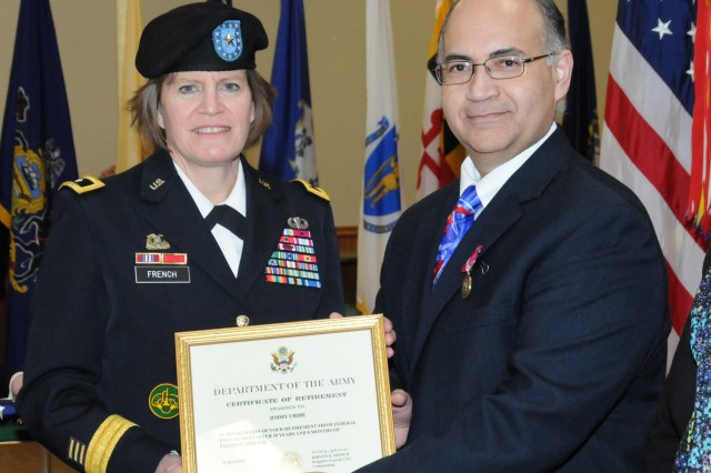 Brig. Gen. Kristin K. French, Joint Munitions Command commanding general, presents Jimmy Uribe his certificate of retirement following more than 30 years of service as a Department of the Army civilian during the Rock Island Arsenal Retirement and Retreat Ceremony, March 26.