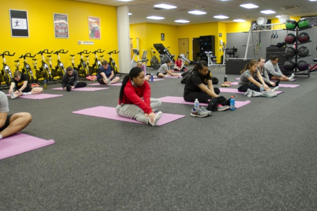 Soldiers of 2nd Infantry Division enrolled in the Pregnancy and Postpartum Physical Training Program warm up during a yoga session at Camp Casey, South Korea March 20. Spouses were invited to wear an empathy belly to simulate the altered center of gravity experienced by the expectant females. (U.S. Army photo by Spc. Lauren Wanda, 1st ABCT Public Affairs)