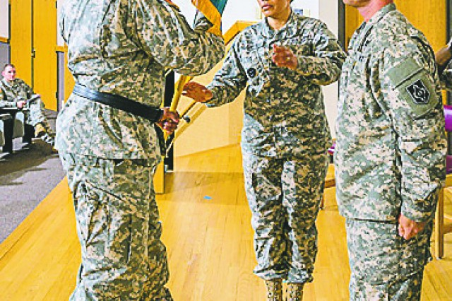 Command Sgt. Maj. Alma Zeladaparedes accepts the NCO Academy's colors from Maj. Gen. Leslie Smith, Maneuver Support Center of Excellence and Fort Leonard Wood commanding general, at an assumption of commandancy ceremony Tuesday in Lincoln Hall Auditorium.