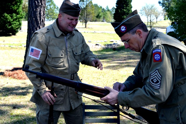 World War II reenactors discuss the equipment used by paratroopers while commemorating the U.S. Army's first mass tactical airborne operation, March 29, 2015. The jump commenced 72 years ago in Camden, S.C.