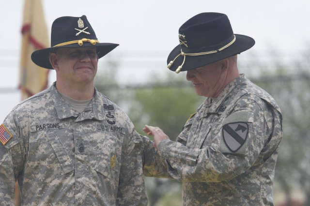 Maj. Gen. Michael Bills, commander of the 1st Cavalry Division, (right) places a 1st Cav. Div. patch on the uniform of Command Sgt. Maj. Berk Parsons, senior enlisted advisor of Division Artillery, 1st Cav. Div., (left) during the activation ceremony of the 1st Cavalry Division Artillery at Cooper Field, here, April 2. (U.S. Army photo by Sgt. Garett Hernandez, 1st Cavalry Division Artillery Public Affairs)