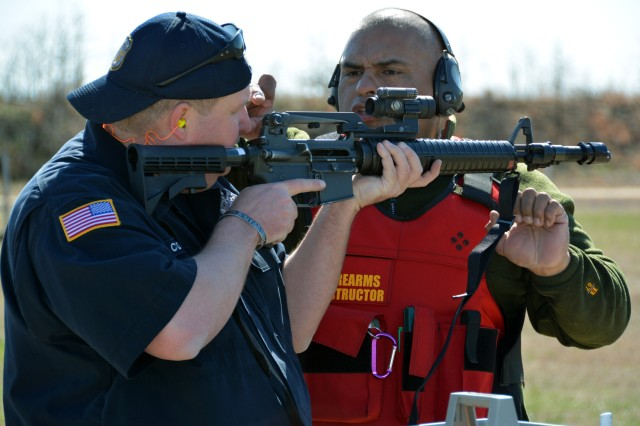 Firearms Instructor and Department of Army Police Officer Daniel Carvajal Jr. (right) instructs fellow Officer Shawn S. Cottingham on how to use the M-68 reflex sight mounted on his M-16 during weapons qualification this week here on U.S. Army Garrison Fort A.P. Hill.
