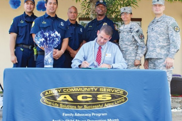 Michael Amarosa, acting deputy garrison commander, U.S. Army Garrison-Hawaii, signs a proclamation declaring April to be Child Abuse Prevention Month, April 1, at the Schofield Child Development Center. Community leaders, including members of the Federal Fire Department, Directorate of Emergency Services and garrison command, participated during the event.