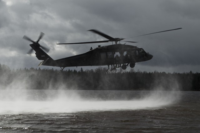 Aviators from the Bravo Company, 3-158th Assault Helicopter Battalion, 12th Combat Aviation Brigade, provide aviation support for helocast training on April 2, 2015, with Soldiers from the Latvian Special Forces over the Daugava River in Latvia.