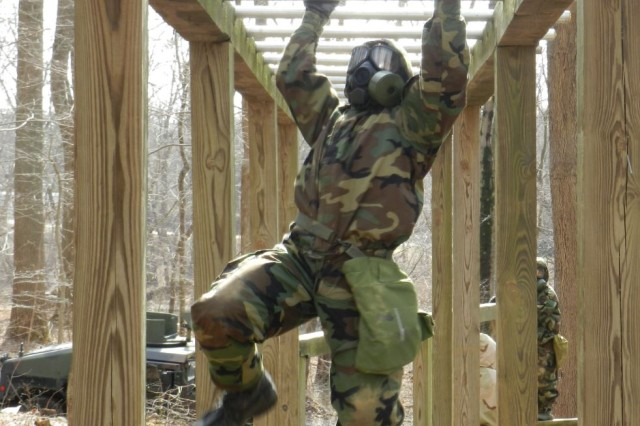 A Soldier from 20th CBRNE Command runs the obstacle course in a chemical suit and gas mask during the inaugural CBRNE Leaders Course at Gunpowder Range, Maryland, March 24.